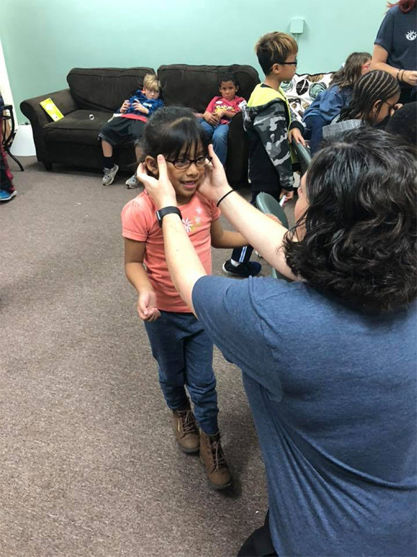 Dr. Reed giving a child her new free glasses